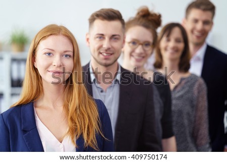 Attractive young businesswoman posing with her team of co-workers in a receding line behind her looking at the camera with a confident smile - stock photo