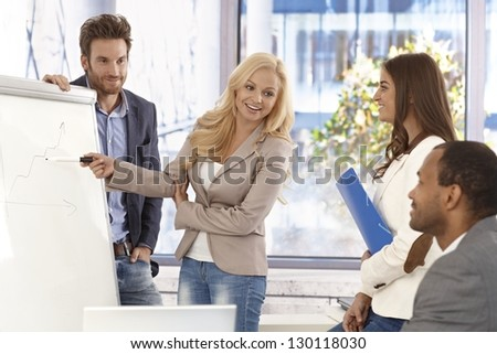 Attractive young businesswoman presenting to colleagues on whiteboard, smiing. - stock photo