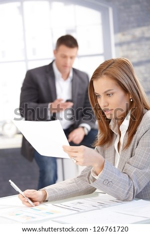 Attractive young businesswoman sitting at desk, busy by working, man texting in background.