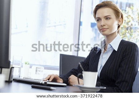 Attractive young businesswoman sitting at desk in bright office, typing on keyboard. - stock photo