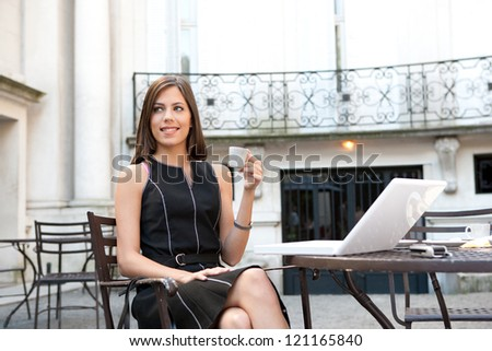 Attractive young businesswoman sitting with her laptop at a coffee shop near classic office buildings in the city, holding a cup of coffee and smiling. - stock photo