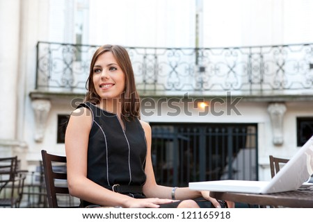 Attractive young businesswoman sitting with her laptop at a coffee shop near classic office buildings in the city, smiling. - stock photo