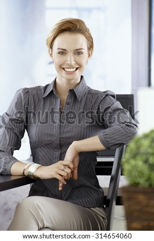 Attractive young businesswoman smiling happy, sitting on chair, looking at camera. - stock photo