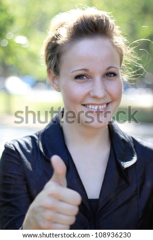 Attractive Young Businesswoman Smiling Thumbs Up - stock photo