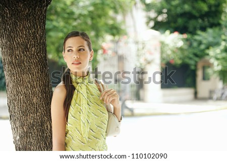Attractive young businesswoman standing under a tree in the city, holding her handbag. - stock photo