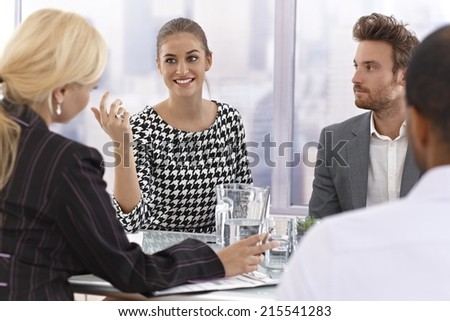 Attractive young businesswoman talking at a meeting, partners listening.