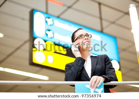 attractive young businesswoman talking on cell phone at airport - stock photo