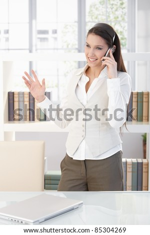 Attractive young businesswoman talking on mobile phone, smiling.?