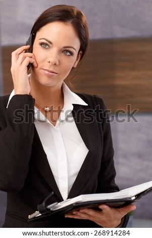 Attractive young businesswoman talking on mobilephone, holding organizer, looking away.