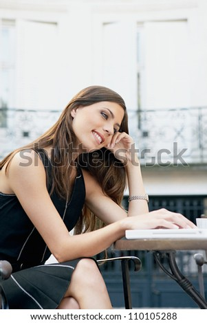 Attractive young businesswoman using a laptop computer while sitting at a coffee shop's terrace table.