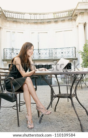 Attractive young businesswoman using a laptop computer while sitting at a coffee shop's terrace table. - stock photo