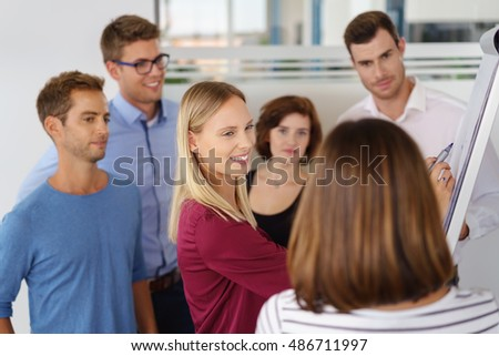 Attractive young businesswoman with her business team grouped around her doing a presentation at a flip chart