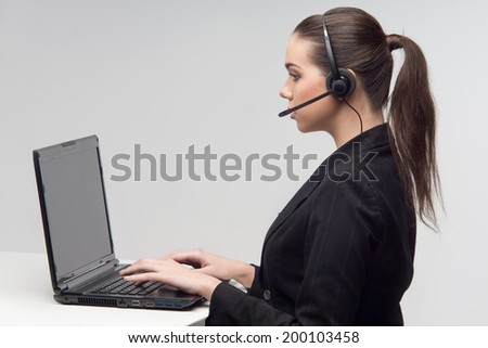 Attractive young businesswoman working at desk, using laptop computer and phone headset , looking at screen. Side view. - stock photo