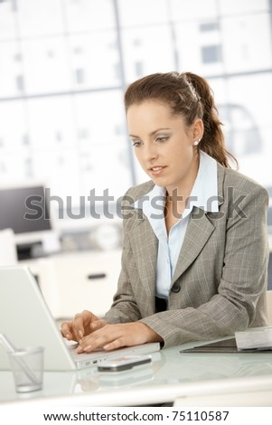 Attractive young businesswoman working on laptop in bright office.?