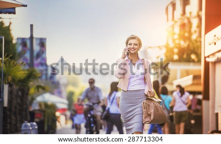 Attractive young businness woman with smart phone in the city - stock photo