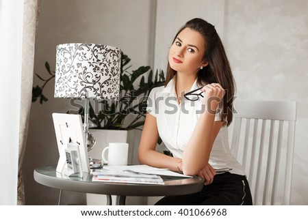 Attractive young bussinesswoman wearing classical clothes and holding glasses sit in  her cabinet at home and preparing to work.