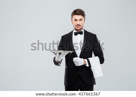 Attractive young butler in tuxedo standing and holding silver empty tray and napkin