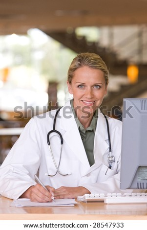 Attractive young caring doctor - stock photo