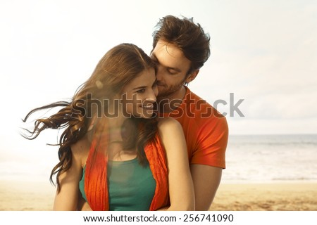 Attractive young casual caucasian brunette woman getting a kiss from boyfriend at beach. Romance, couple, smiling, embracing. Lens flare, sand and copyspace. - stock photo
