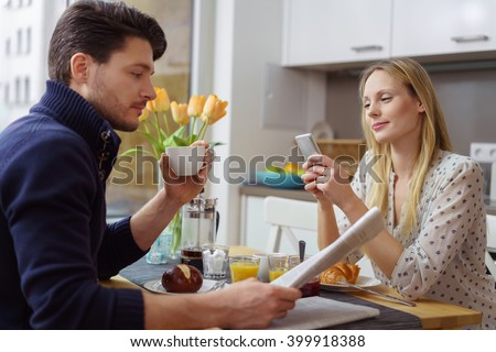 Attractive young Caucasian couple distracted at table with newspaper and cell phone while eating breakfast - stock photo
