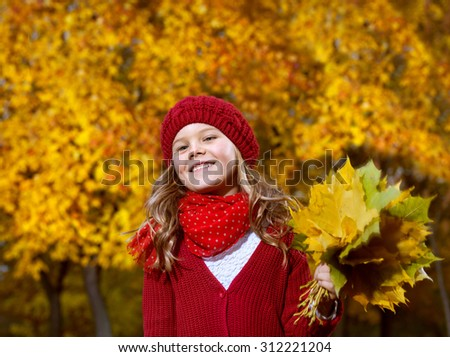 attractive young caucasian little girl in warm red colorful clothing  on yellow leaves outdoors smiling happy child kid walk - stock photo
