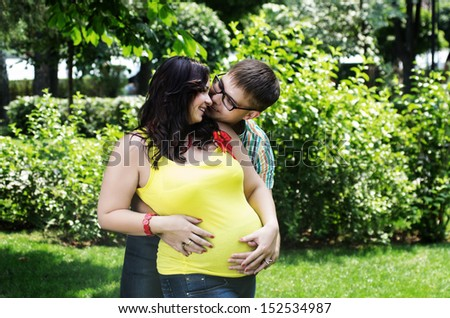 Attractive young caucasian pregnant couple on the lawn at  park
