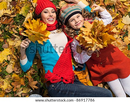 attractive young caucasian woman and girl in warm colorful clothing  lying on yellow leaves outdoors smiling