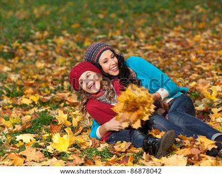 attractive young caucasian woman and girl in warm colorful clothing  on yellow leaves outdoors smiling