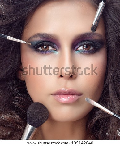 attractive young caucasian woman closeup portrait isolated on white looking at camera studio shot face macro skin makeup eyes hands brushes - stock photo