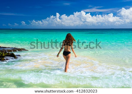 Attractive young caucasian woman in black swimsuit looking on sea at tropical beach