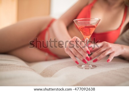 Attractive young Caucasian woman in red lingerie lying on a bed with a red cocktail.