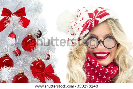 attractive young caucasian woman in warm clothing  in studio isolated on white smiling hat glasses christmas tree red balls - stock photo