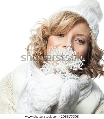 attractive young caucasian woman in warm clothing  in studio isolated on white smiling snowflake - stock photo