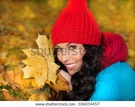 attractive young caucasian woman in warm colorful clothing  on yellow leaves outdoors smiling