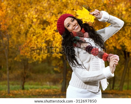 attractive young caucasian woman in warm colorful clothing  on yellow leaves outdoors smiling - stock photo