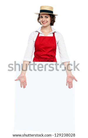 Attractive young chef presenting blank whiteboard. Ad concept. - stock photo