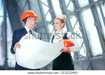 Attractive young construction team is discussing their project. They are standing and holding a blueprint. The engineers are looking at each other and smiling. The man is wearing a helmet - stock photo