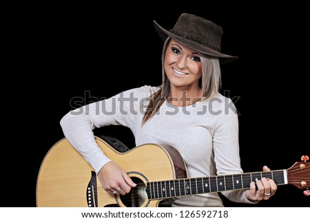 Attractive young country woman playing acoustic guitar - stock photo