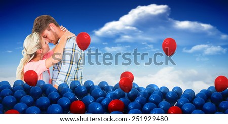 Attractive young couple about to kiss against bright blue sky with clouds - stock photo