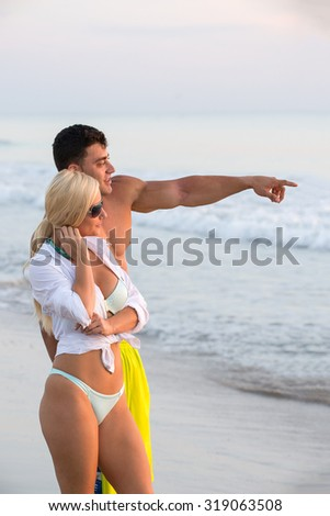attractive young couple at beach at sunrise - stock photo