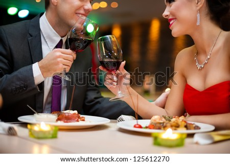 Attractive young couple drinking red wine in a romantic atmosphere - stock photo