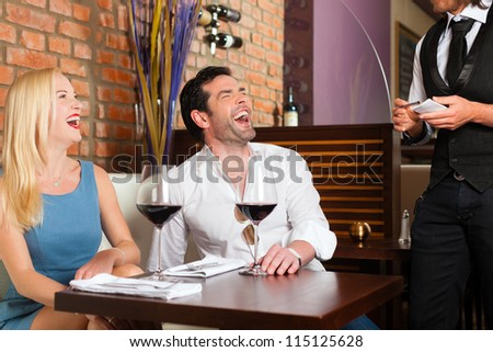 Attractive young couple drinking red wine in restaurant or bar, the waiter is taking the order - stock photo