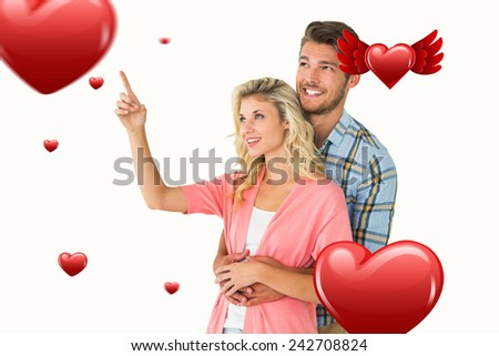 Attractive young couple embracing and looking against hearts - stock photo