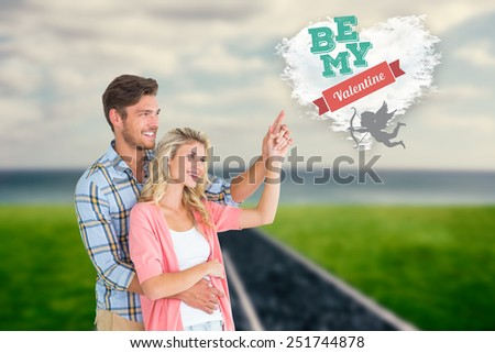 Attractive young couple embracing and pointing against cloud heart - stock photo