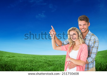Attractive young couple embracing and pointing against green field under blue sky - stock photo