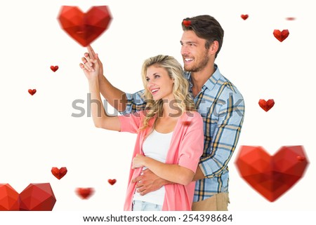 Attractive young couple embracing and pointing against hearts - stock photo