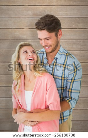 Attractive young couple embracing and smiling against wooden planks - stock photo