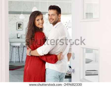 Attractive young couple embracing, looking back over shoulder in entrance door at home. Both smiling, looking at camera. - stock photo