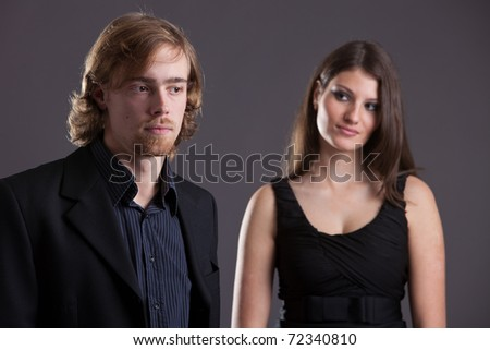 Attractive young couple flirting from a distance. Focus on the man - stock photo
