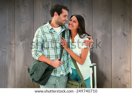 Attractive young couple going on their holidays against wooden planks - stock photo